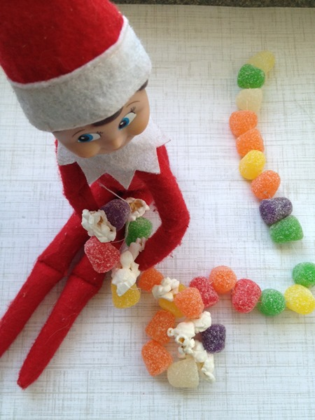 Elf on the Shelf making a gumdrop and popcorn garland