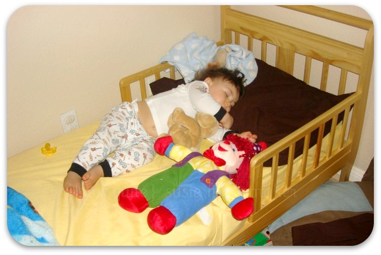 sleeping baby in toddler bed