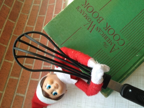 Elf on the Shelf baking with a whisk and cookbook
