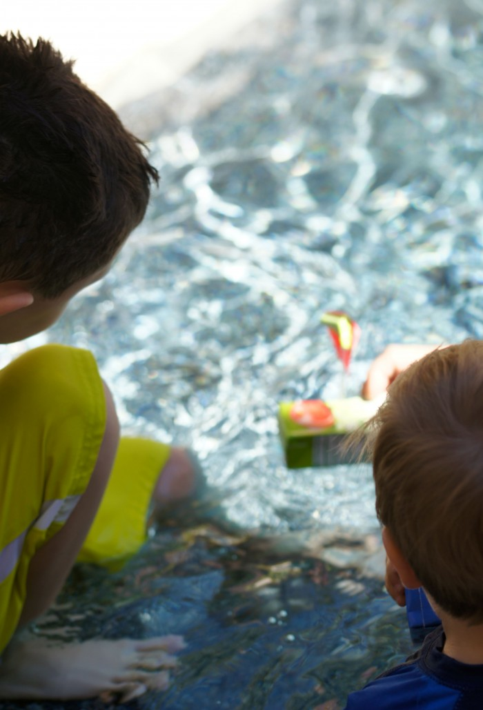 Looking for fun and free at home outdoor summer activities for kids? These DIY Juice Box Boats are a great way to take up an afternoon- build them by upcycling things from around the house and then set sail!