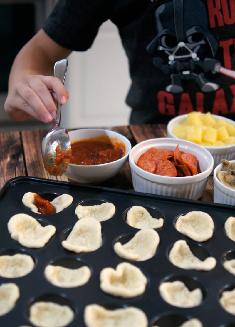 If you're looking for a delicious, easy to customize appetizer for your next football party or tailgate, try these easy Mini Pizza Bites! You can add whatever toppings you like {think mushrooms, pepperoni, sausage, pineapple, bacon, olives- whatever!} and when you bake them in the Wilton Perfect Results Mega Muffin tin you get 48 of them per batch! That's one way to win on game day!