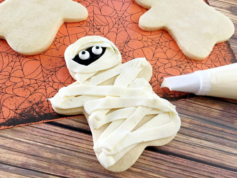 These easy DIY Homemade Halloween cookies taste like sugar cookies with a hint of pumpkin- and they are decorated like mummies! While they look super cute, they are easy to make and they're one of my favorite Halloween recipes for kids.