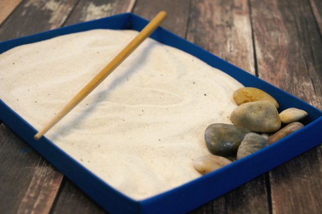 Zen gardens are beautiful places for meditation and to get new ideas- but not everyone has room in their backyard for a dedicated zen zone {not to mention the weather isn't always cooperative!} Bring the zen garden indoors with this super easy upcycled craft idea! Make a miniature desktop DIY sand Zen Garden using mostly materials you have at home {this craft costs under $5 to make!} This project can even function as home décor and even as a fidget tool.