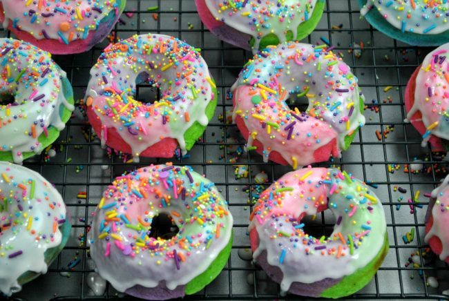 These DIY homemade baked donuts are better than good- they're magical! Rainbow colored with a custom unicorn sprinkle blend, these are sure to be the hit of any birthday party or even just weekend breakfast! Learn how to make these easy and cute sprinkles donuts- one of my favorite recipe ideas!
