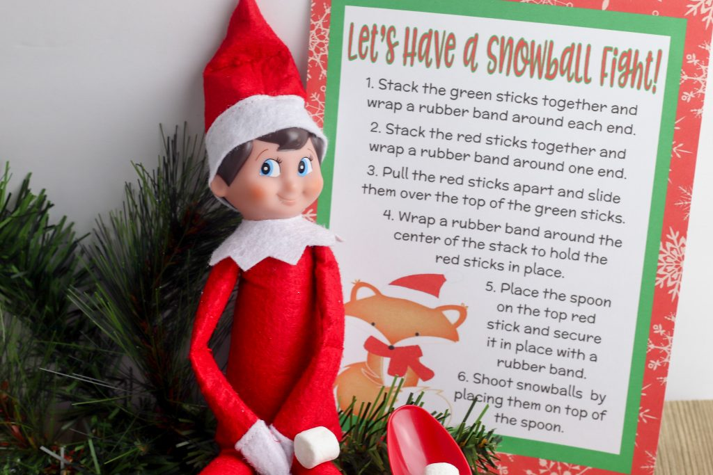 Weeks after their return, Scout Elves start to run out of ideas. Help them keep the fun going for boys or for girls long after their Welcome back arrival day with this new fun and easy Elf on the Shelf Idea- a Snowball Fight with DIY Make Your Own Catapult! The free printable makes it easy for adults- and it's fun for kids!